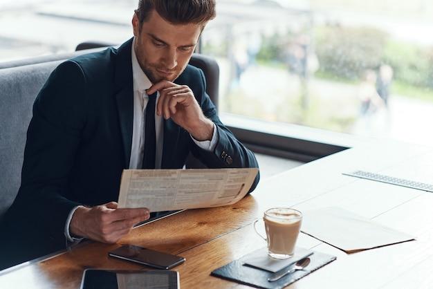 Beau jeune homme d'affaires en costume complet lisant le menu alors qu'il était assis dans le restaurant