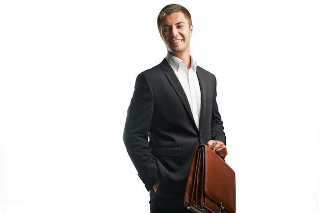 Beau jeune homme d'affaires en costume noir tenant une valise