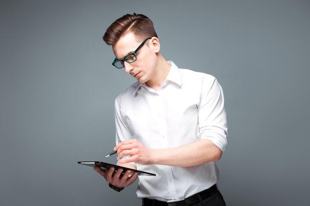 Beau jeune homme d'affaires dans une montre coûteuse, lunettes noires et chemise blanche tenir tablette et stylo
