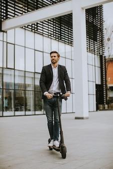 Beau jeune homme d'affaires dans un vêtement décontracté équitation un scooter électrique par un immeuble de bureaux lors d'une réunion d'affaires