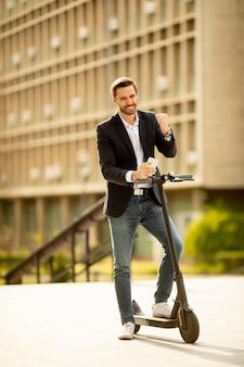 Beau jeune homme d'affaires dans un vêtement décontracté recevant de bonnes nouvelles sur téléphone mobile en se tenant debout sur un scooter électrique par un immeuble de bureaux