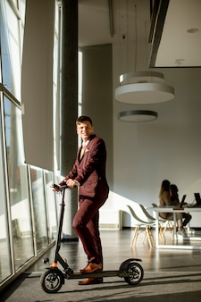 Beau jeune homme d'affaires debout près de la fenêtre du bureau avec scooter électrique