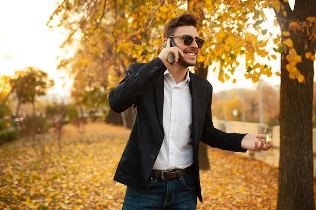 Beau jeune homme d'affaires élégant, heureux et souriant, parlant au téléphone