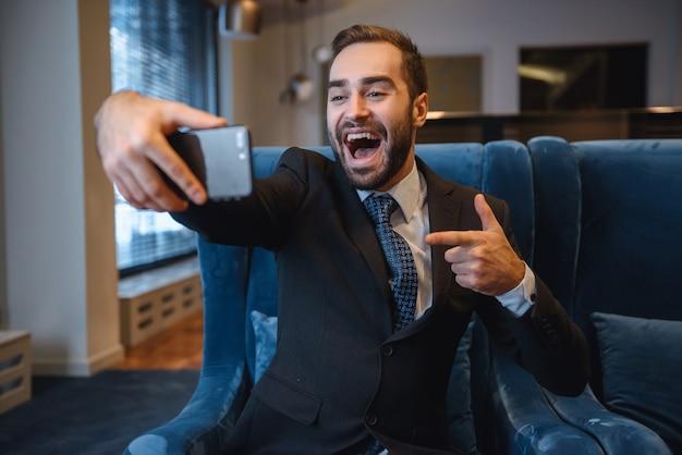 Beau jeune homme d'affaires excité portant un costume assis dans le hall de l'hôtel, à l'aide d'un téléphone portable, en prenant un selfie, en pointant