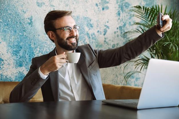 Beau jeune homme d'affaires habillé en costume assis au café à l'intérieur, boire du café, prendre un selfie
