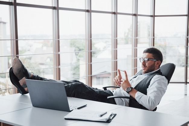 Beau jeune homme d'affaires avec des lunettes tenant ses jambes sur la table en regardant un ordinateur portable au bureau