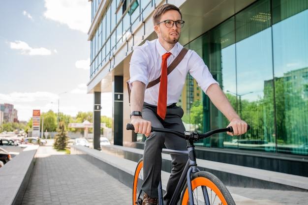 Beau jeune homme d'affaires à lunettes et tenues de soirée assis sur un vélo et se déplaçant sur la route le long de l'architecture moderne