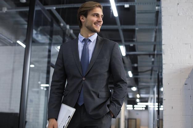 Beau jeune homme d'affaires marchant dans le couloir du bureau.