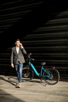 Beau jeune homme d'affaires marche de son vélo électrique et à l'aide de téléphone portable