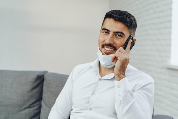 Beau jeune homme d'affaires avec masque facial, parler au téléphone, portrait