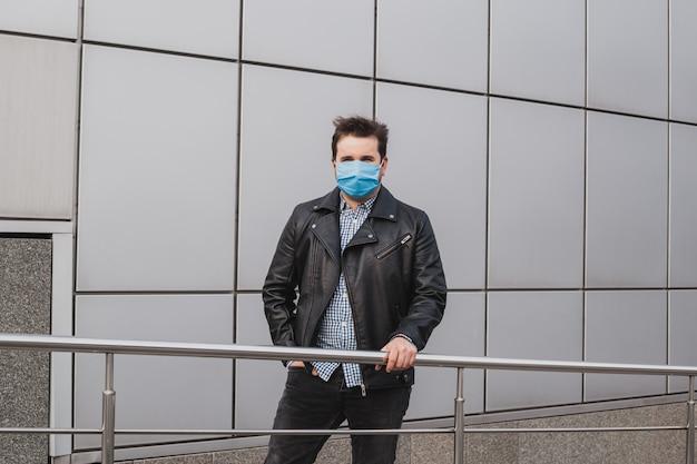 Un beau jeune homme d'affaires en masque sur fond d'immeuble de bureaux fermés, coronavirus, maladie, infection, quarantaine, masque médical