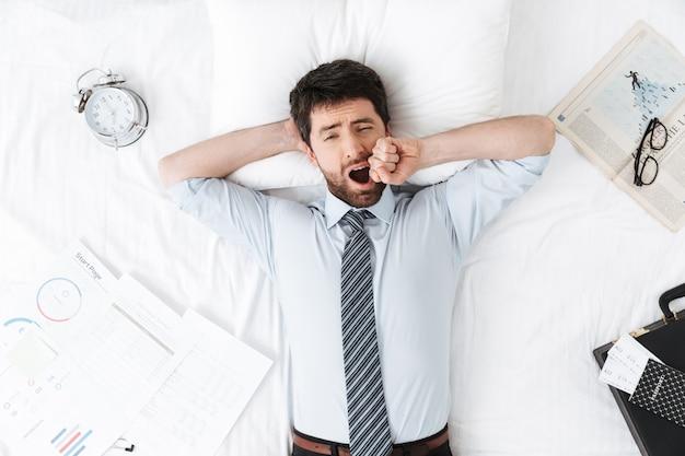Beau jeune homme d'affaires le matin au lit se trouve le bâillement