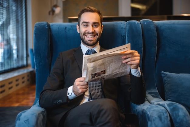 Beau jeune homme d'affaires pensive portant costume assis dans le hall de l'hôtel, lisant le journal