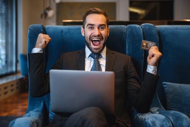 Beau jeune homme d'affaires portant costume assis dans le hall de l'hôtel, à l'aide d'un ordinateur portable, montrant une carte de crédit en plastique