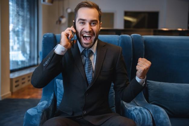 Beau jeune homme d'affaires portant costume assis dans le hall de l'hôtel, à l'aide de téléphone portable, célébrant le succès