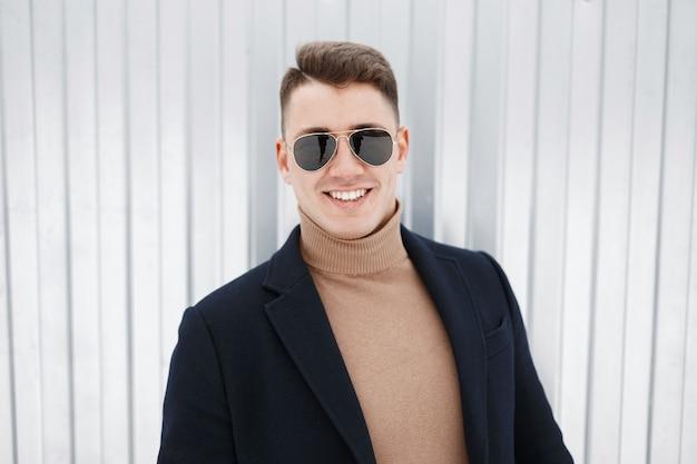 Beau jeune homme d'affaires prospère avec un sourire charmant dans des lunettes de soleil élégantes dans un manteau élégant coûteux dans un pull en tricot