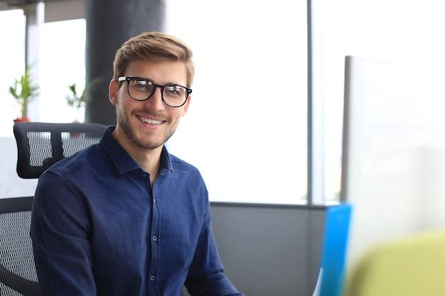 Beau jeune homme d'affaires regardant la caméra et souriant alors qu'il était assis au bureau.