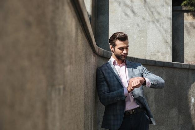 Beau jeune homme d'affaires en regardant la montre.