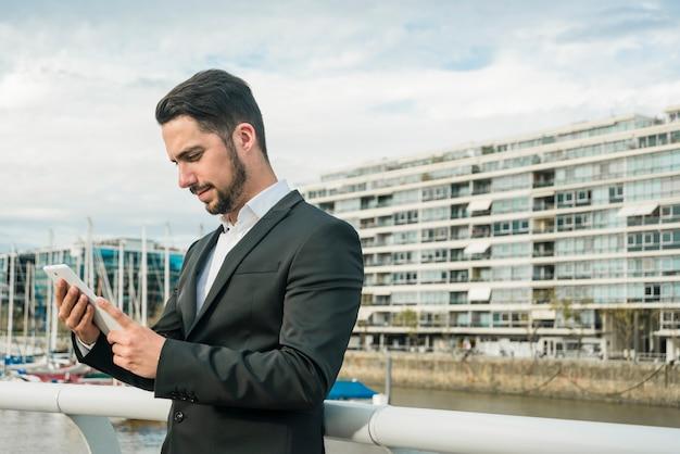 Beau jeune homme d'affaires en regardant téléphone mobile