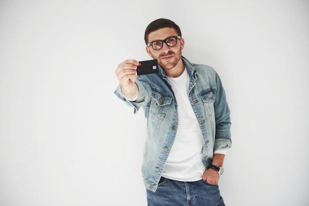 Beau jeune homme d'affaires en tenue décontractée tenant une carte de crédit dans les poches sur un fond blanc. le concept de trading sur internet et la facilité de la monnaie électronique.