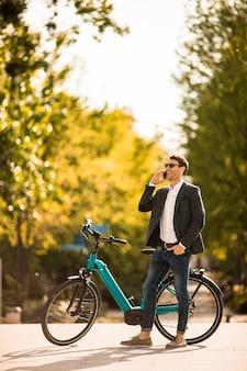 Beau jeune homme d'affaires sur le vélo électrique à l'aide de téléphone mobile