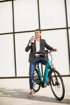 Beau jeune homme d'affaires sur le vélo électrique avec une tasse de café à emporter