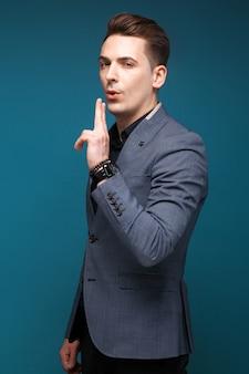 Beau jeune homme d'affaires en veste grise, montre coûteuse et chemise noire