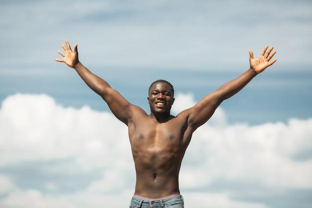 Beau jeune homme africain athlétique avec les bras levés