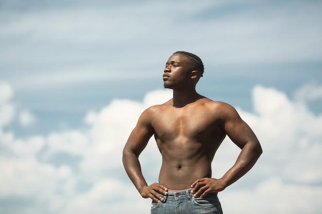 Beau jeune homme africain athlétique contre le ciel