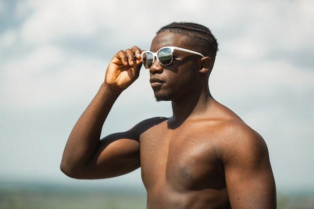 Beau jeune homme africain athlétique portant des lunettes de soleil