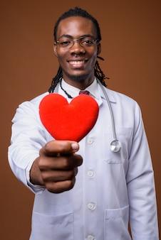 Beau jeune homme africain médecin sur fond marron
