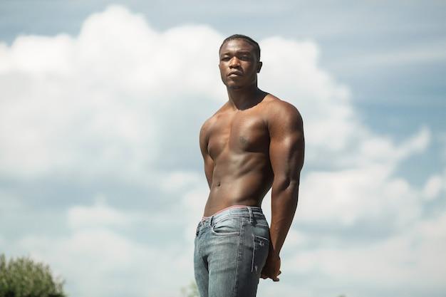 Beau jeune homme africain avec des muscles contre le ciel