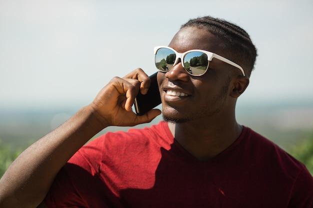 Beau jeune homme africain portant des lunettes de soleil avec téléphone portable