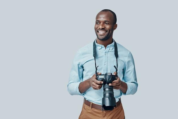 Beau jeune homme africain regardant loin et souriant tout en se tenant contre le mur gris