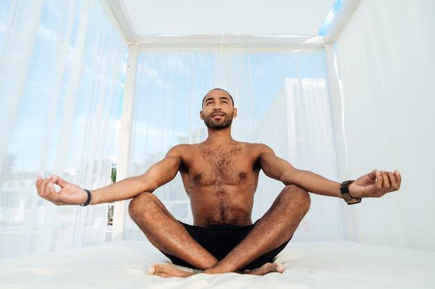 Beau jeune homme africain en short assis et méditant sur le lit de plage
