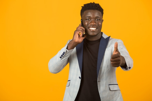 Beau jeune homme africain en veste avec le geste de la main, avec téléphone mobile