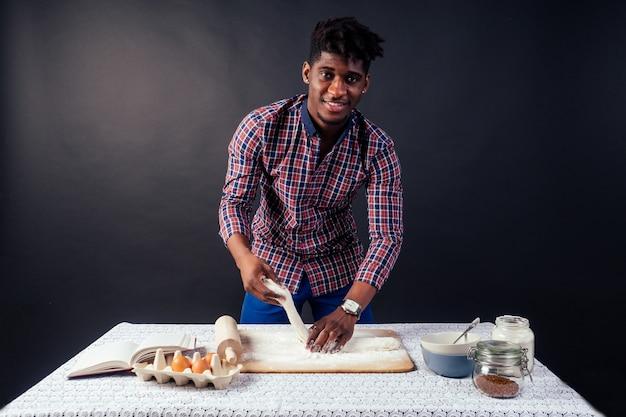 Beau et jeune homme afro-africain préparant des gâteaux faits maison tarte américaine à partir de mains de pâte fraîche sales par la farine, sur la table se trouvent des œufs, un rouleau à pâtisserie et un livre de recettes sur fond noir dans le studio