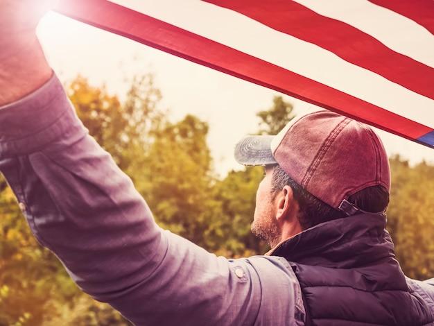 Beau jeune homme agitant un drapeau américain