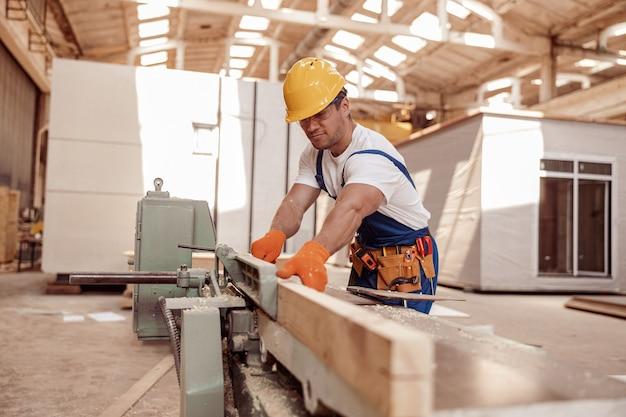 Beau jeune homme à l'aide d'une machine à bois en atelier