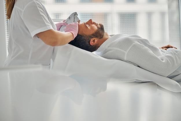 Beau jeune homme allongé sur un lit de repos tout en recevant un traitement facial au laser au centre de bien-être