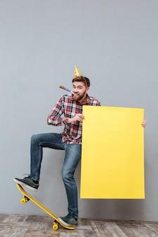 Beau jeune homme anniversaire barbu sur planche à roulettes tenant un tableau blanc