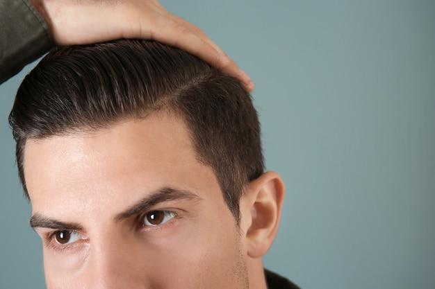 Beau jeune homme appliquant de l'argile pour cheveux sur gris