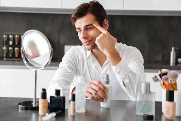 Beau jeune homme appliquant des produits de maquillage et de beauté
