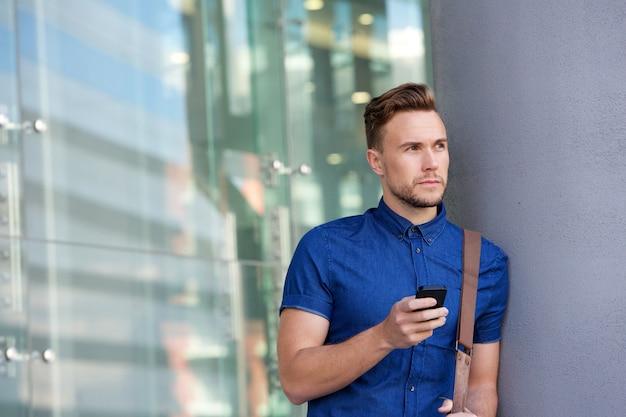Beau jeune homme, appuyé, mur, dehors, à, téléphone portable