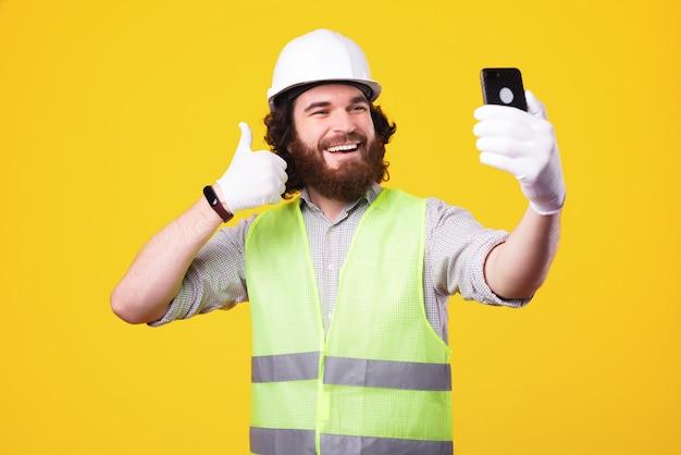 Beau jeune homme architecte prenant selfie avec smartphone et montrant le pouce vers le haut