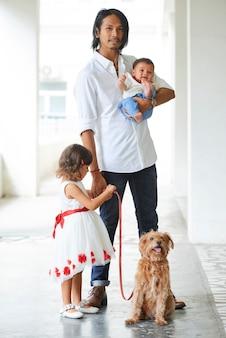 Beau jeune homme asiatique élégant marchant avec son petit fils, sa fille et son chien mignon en laisse