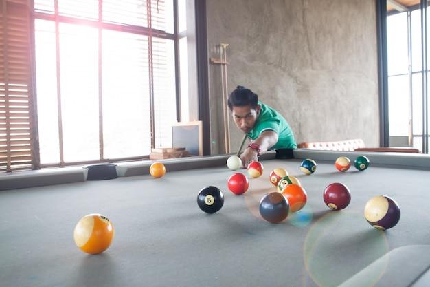 Beau jeune homme asiatique jouant au billard à la maison, mise au point sélective sur le ballon
