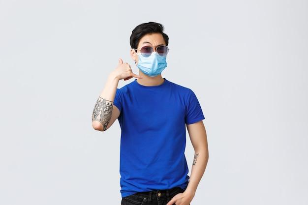 Beau jeune homme asiatique sûr de lui, homme à lunettes de soleil et masque médical, flirter, faire appel téléphonique signe moi