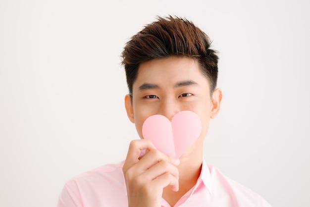 Beau jeune homme asiatique tenant la saint-valentin en forme de coeur de papier