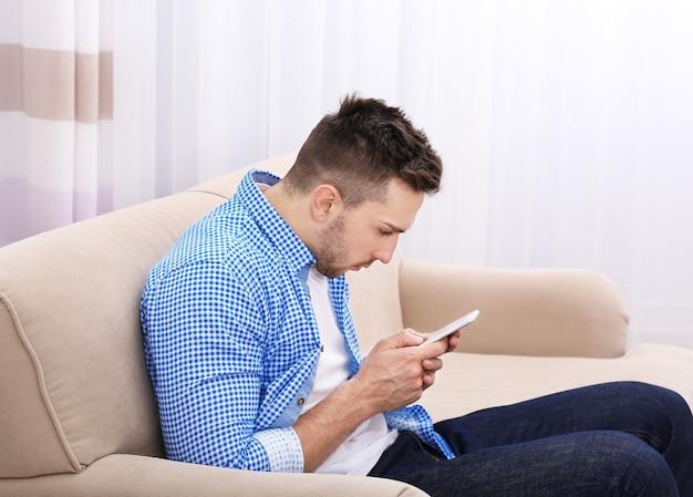 Beau jeune homme assis sur le canapé à la maison. concept de posture incorrecte